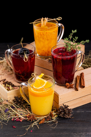 Vertical image of fruit tea ceremony with orange, cinnamon and berries at wooden table background.
