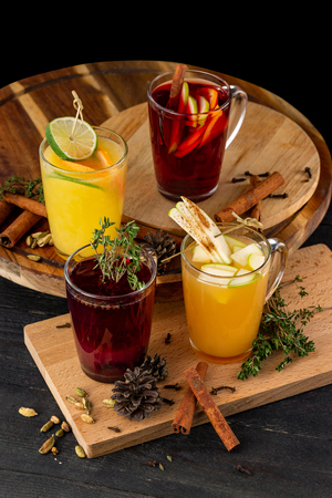Vertical image of glasses of mulled wine with apple, orange, cinnamon at wooden table background. Imagens