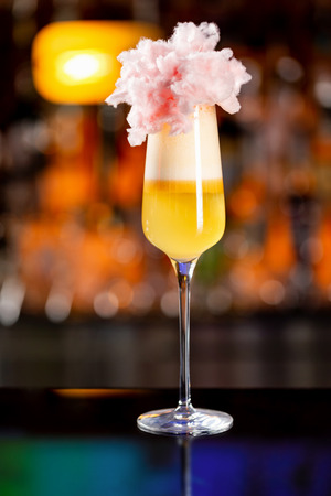 Closeup vertical glass of yellow layered cocktail decorated with cotton candy at bar counter background.