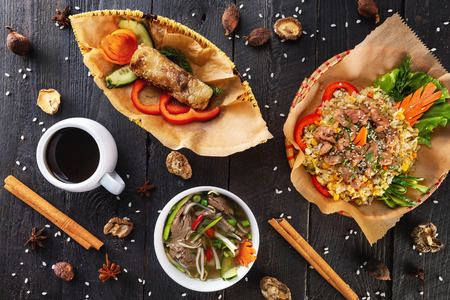 Top view image of vietnamese food - pho soup, spring roll, fried rice and coffee at wooden table background. Imagens - 122755152
