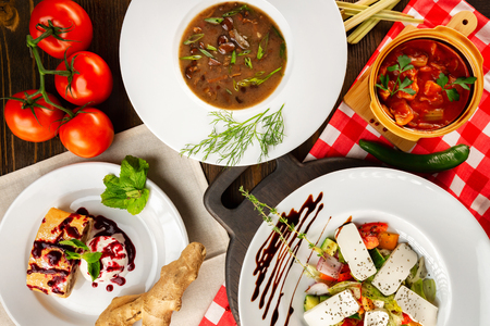 Top view european style dinner with soup, dessert, salad and meat at decorated table background. Imagens