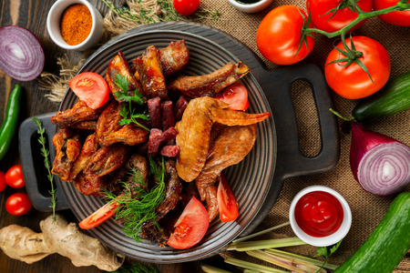 Top view board of various meat set of fried chicken, sausages at decorated with vegetables wooden table background.