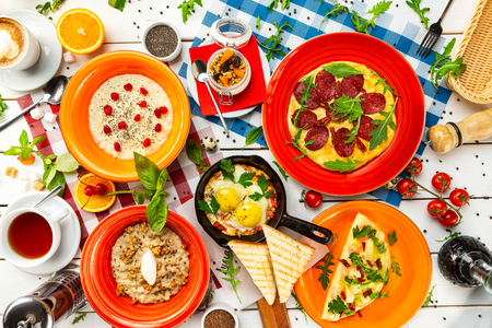 Top view italian style dinner with teas, coffee, dessert, cereals and fried eggs at decorated wooden table background. Imagens