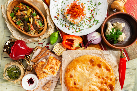 Top view image of traditional georgian lunch with various meals and ingredients at decorated table background.