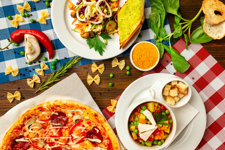 Top view image of italian style business lunch of pizza, soup and salad at wooden table background.