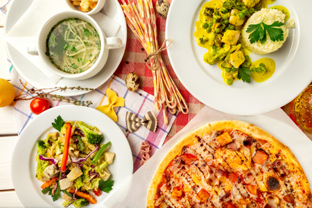 Top view image of italian style business lunch of pizza, soup, steamed vegetables and salad at wooden table background. Imagens