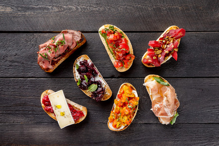 Top view italian bruschettas set at wooden board background. Stock Photo
