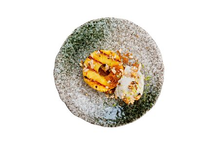 Plate of smoked coconut milk icecream served with pineapple and puffed rice at concrete table background.