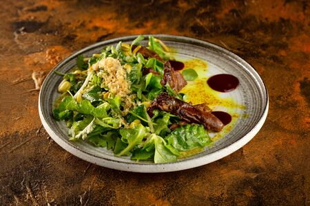 Plate of salad with duck breast served with hoisin sauce ay textured brown table background.