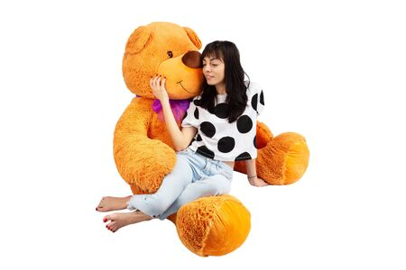 Portrait of young girl hugging a huge teddy bear isolated at white background.