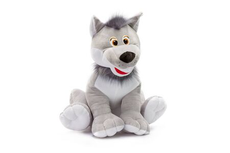 Closeup toy grey soft wolf sitting at isolated white background.
