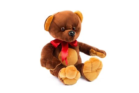 Image of brown toy teddy bear sitting at white isolated background.