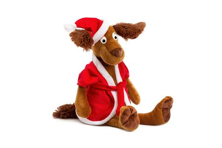 Image of brown fluffy funny toy dog in christmas red suit sitting at isolated white background.