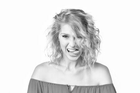 Black and white portrait of young caucasian woman with disgusted face expression isolated at white background. Irritated girl is showing grimace touching teeth with toungue.