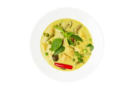 Top view plate of thraditional thailand meal - green curry with chicken and eggplants served in a plate isolated at white background.