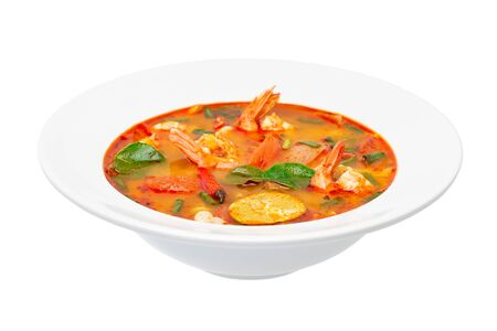 Closeup plate of traditional thai soup - tom yum kung isolated at white background.