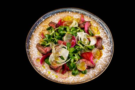 Closeup plate of roast beef salad with radish and fennel isolated at black background.