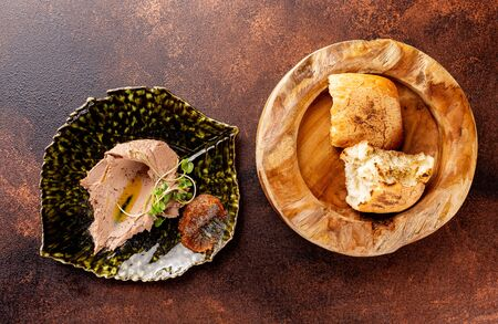 Top view image of chicken pate served on a plate with crispy bread at brown textured background.