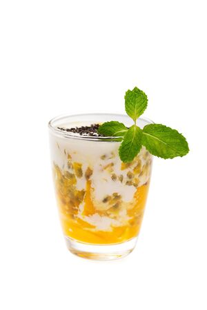 Closeup glass of healthy tropical fruit smoothie with mango, passion fruitc coconut milk and chia seeds decorated with mint isolated at white background. Stok Fotoğraf