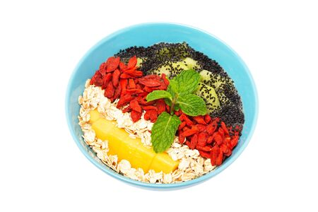 Closeup mage of sweet vegan superfood dessert as healthy lifestyle concept. Bowl of smoothie with kiwi, mango, oats, goji berries, quinoa and chia seeds isolated at white background. Stok Fotoğraf