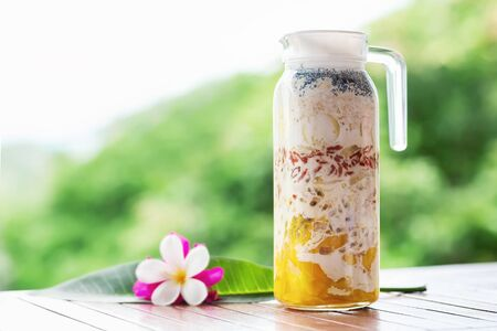 Jug of superfood layered smoothie with tropical fruits and berries at wooden table decorated with flowers at green tropical blurred background. Detox and healthy lifestyle.