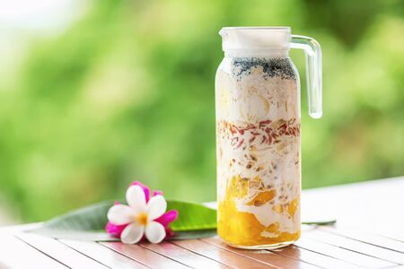 Pitcher with superfood layered smoothie with tropical fruits and berries at wooden table decorated with flowers at green tropical blurred background. Detox and healthy lifestyle.