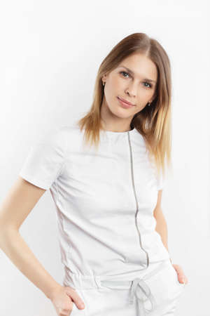 Young attractive smiling female doctor in uniform  is standing  isolated at white background. Concept of beauty industry