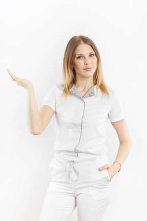 Young female doctor in uniform  is standing with showing gesture isolated at white background. Promotion