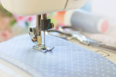 Blurry background of sewing machine working with blue fabric