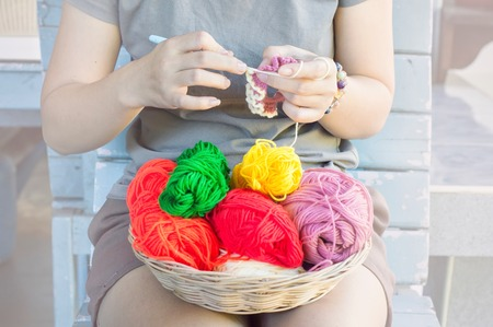 Close up hand of woman knitting colorful wool Stock Photo