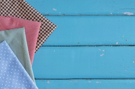 Multicolored fabric on blue wooden table for sewing background