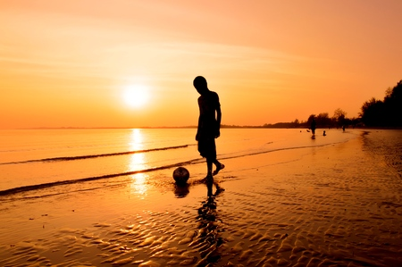 Silhouette of boy playing ball on the beach at sunset