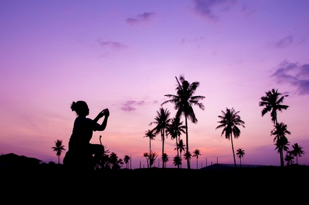 Silhouette of woman taking smart phone at coconut field with twilight sky