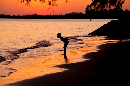 Silhouette of boy standing on the beach at sunset