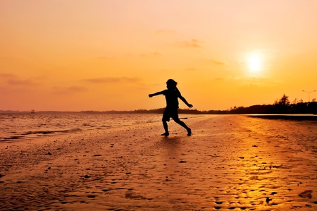 Silhouette of girl running on the beach at sunset