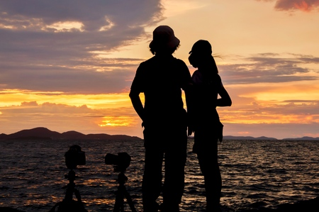 Silhouette of couple standing on the beach at sunset