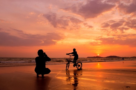 Silhouette father taking a picture of his son on bicycle at the beach with sunset sky