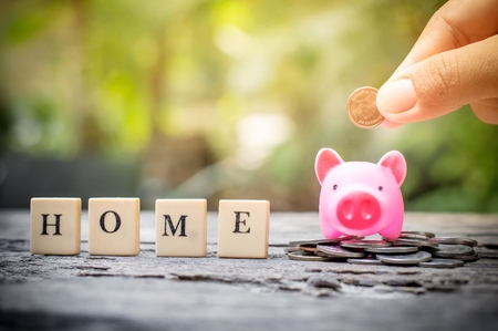 Business concept, hand putting coins in pink piggy bank for home Banco de Imagens