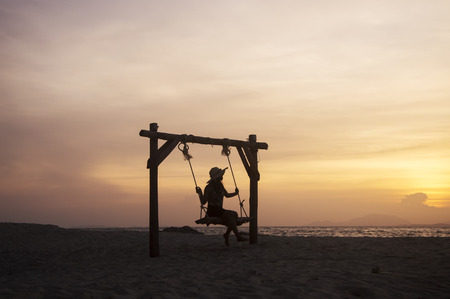 Young woman sitting on a swing at the beach with sunset sky Banco de Imagens