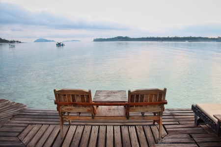 Two wooden chair on wooden floor with blue sea background Banco de Imagens