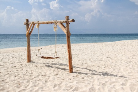 Wooden swing on the sand beach for summer holiday concept.