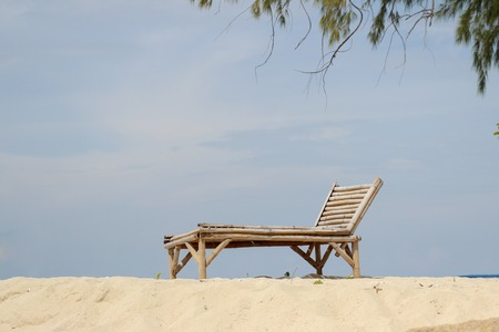 Wooden chair on the sand beach for summer concept