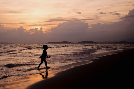 Silhouette of boy playing on the beach with sunset sky