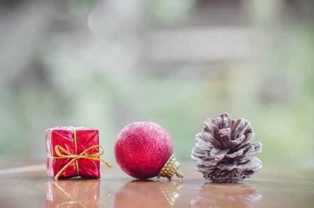 Red gift box, red ball and pine cone for Christmas decoration background