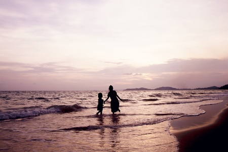 Silhouette of children playing on the beach at sunset Banco de Imagens