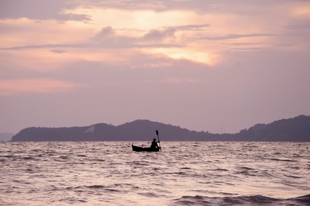 Silhouette of people rowing boat on the sea at sunset Banco de Imagens