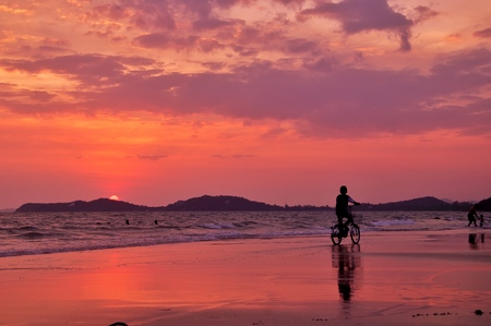Silhouette of boy ride a bicycle on the beach with sunset sky