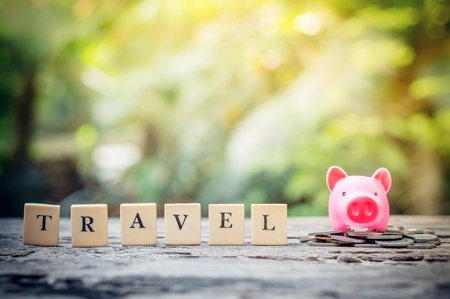 Business concept, hand putting coins in pink piggy bank for travel Banco de Imagens - 123010262