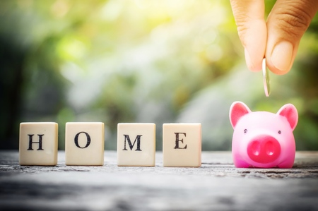 Business concept, hand putting coins in pink piggy bank for home Banco de Imagens - 123010264