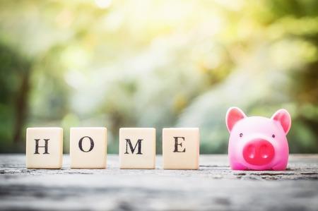 Business concept, saving coins with pink piggy bank for home Banco de Imagens - 123010265
